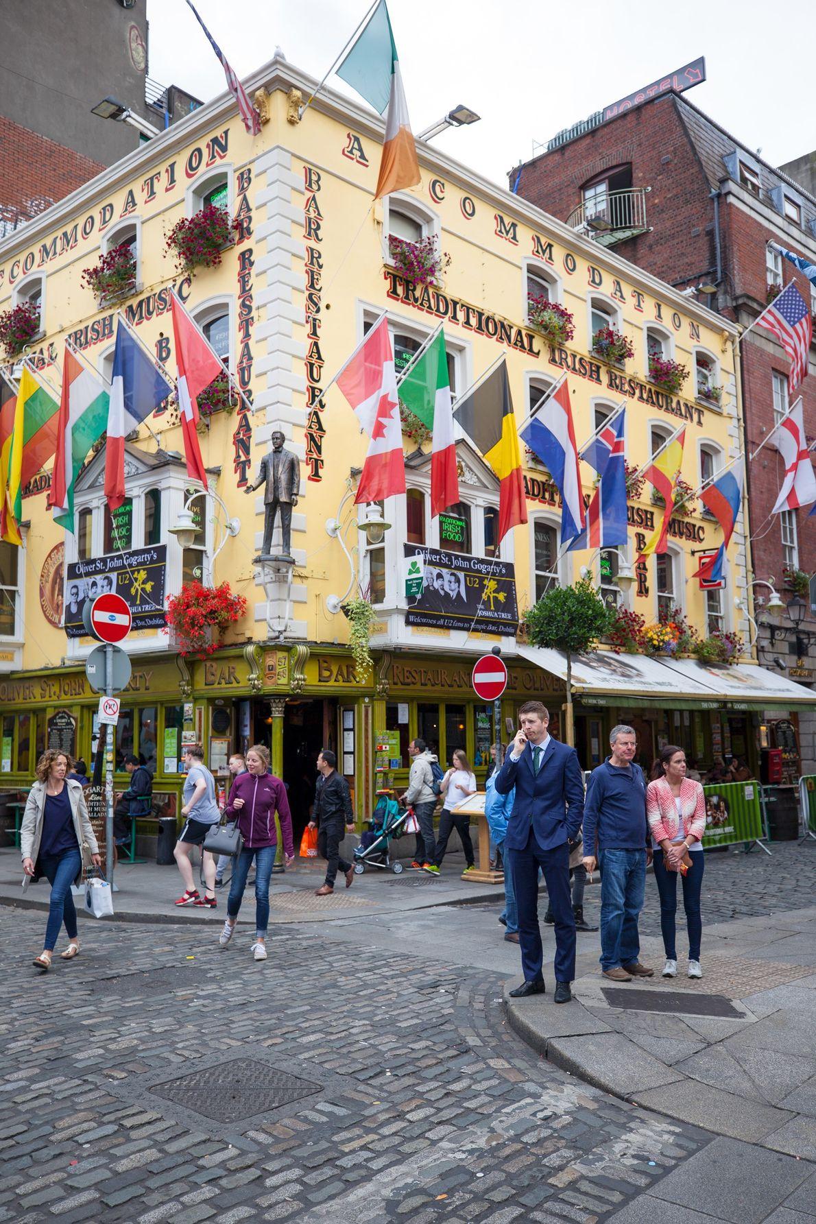 """Une piétonne marche à côté du bar engorgé """"Temple Bar"""", dans le district de Dublin."""