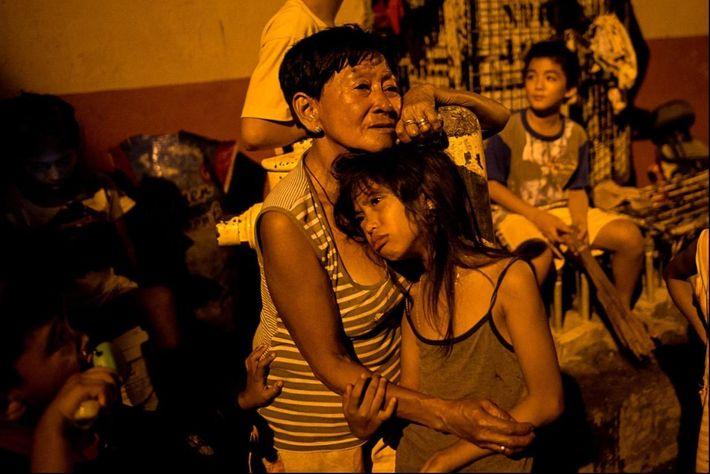 La mère d'Enrico Ranho réconforte sa petite-fille Erica, âgée de 8 ans, témoin de l'assassinat de ...