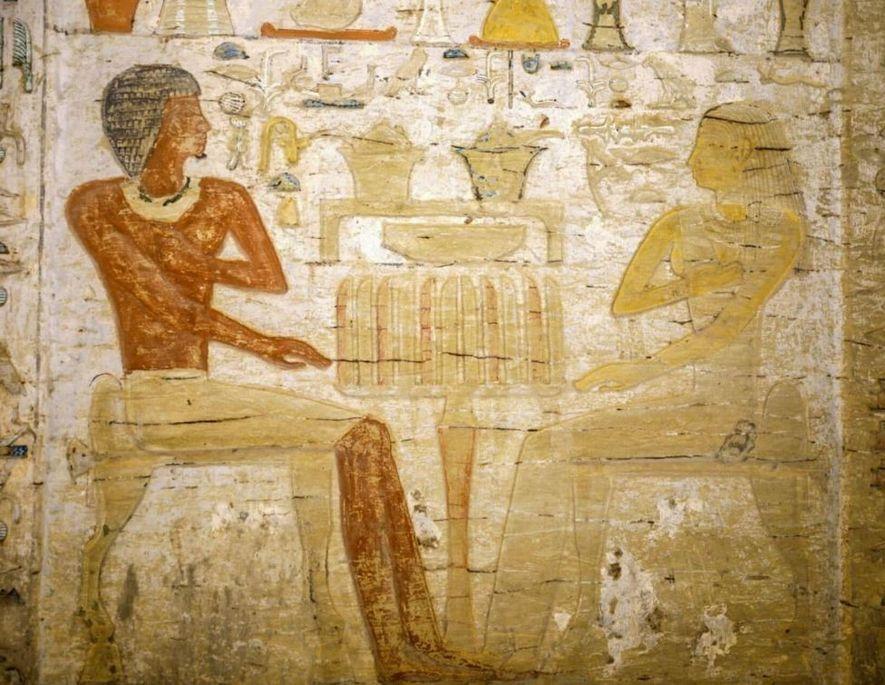 Le défunt, un prêtre nommé Wahtye, est assis à une table d'offrandes avec son épouse.