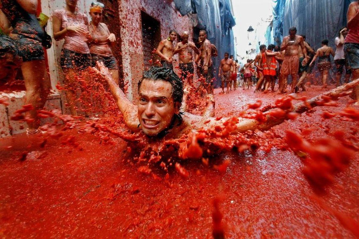 Un homme glisse sur des tomates lors des festivités de la Tomatina à Buñol, en Espagne.