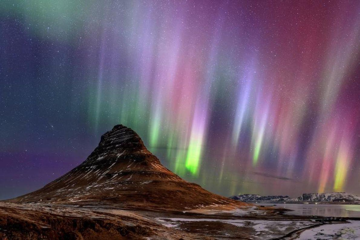 Des aurores boréales ruissellent sur la montagne Kirkjufell, située sur la péninsule Snæfellsnes, en Islande.
