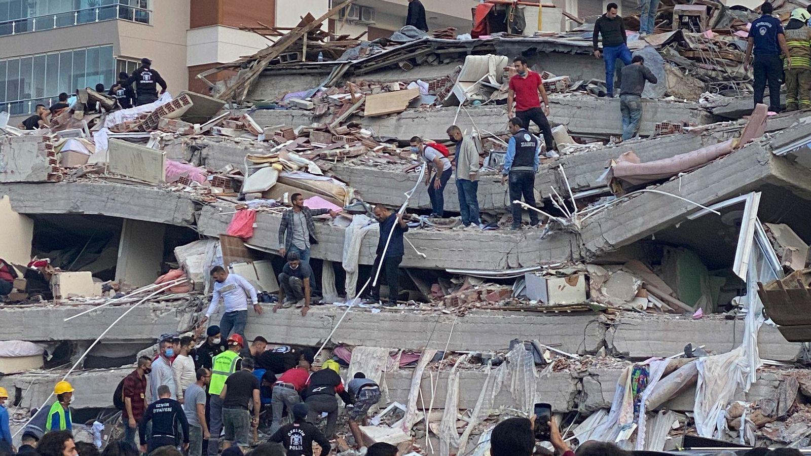 Secouristes et locaux fouillent les décombres d'un bâtiment effondré à la recherche de survivants à Izmir, ...