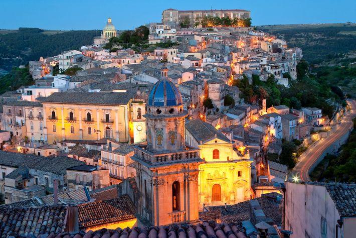Les lampadaires flamboient au crépuscule à travers la ville de Raguse, en Italie.