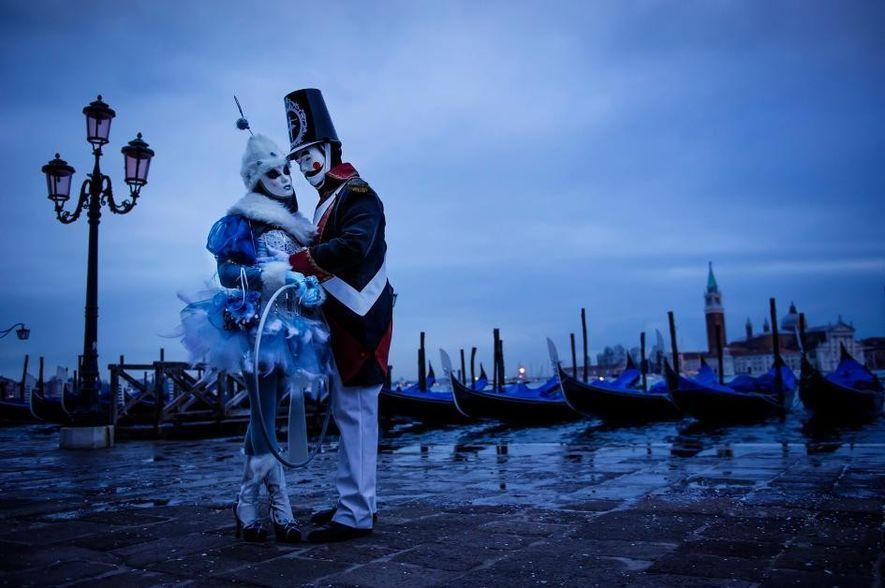 Des carnavaliers prennent la pose dans leurs costumes au bord de l'eau.