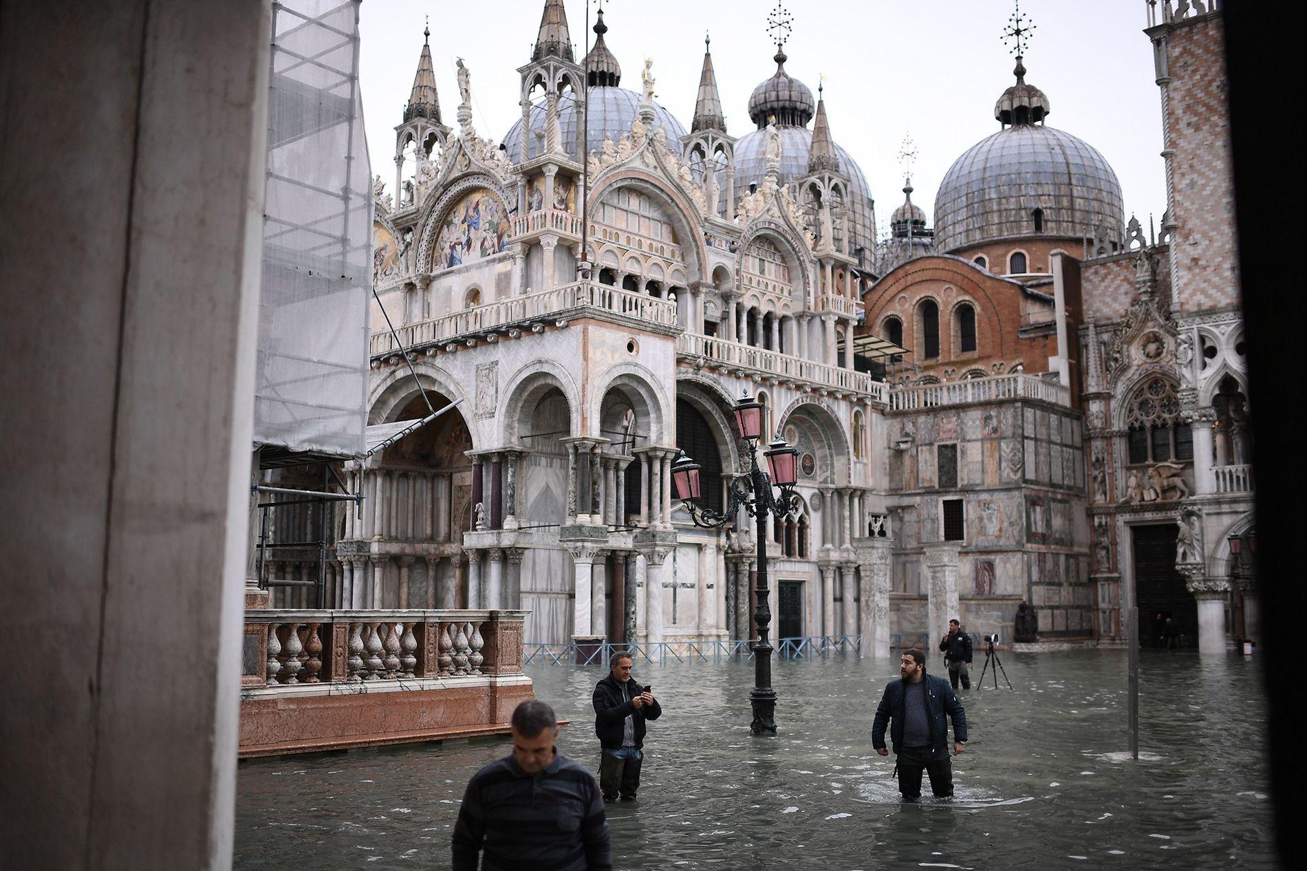 Après avoir enfilé leurs cuissardes, des piétons traversent la place Saint-Marc inondée à Venise. Une marée ...