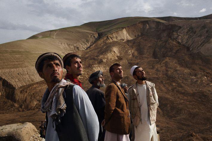 Des villageois regardent des hélicoptères de l'armée survoler les sites de deux glissements de terrain qui ...