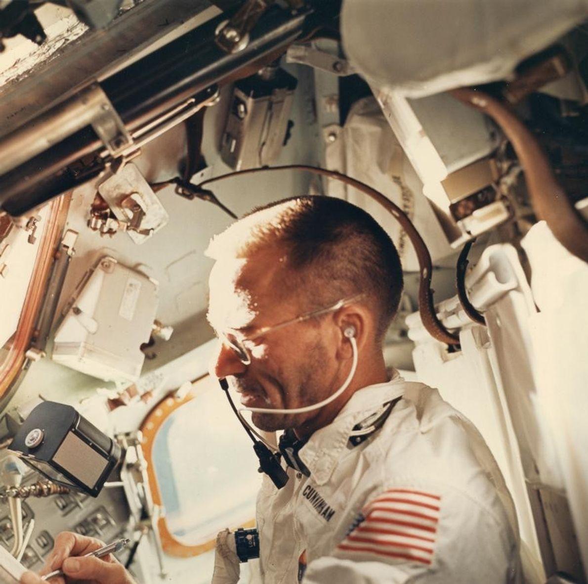 Un appareil photo Hasselblad 70 mm flotte au-dessus de la main droite de l'astronaute Walter Cunningham ...
