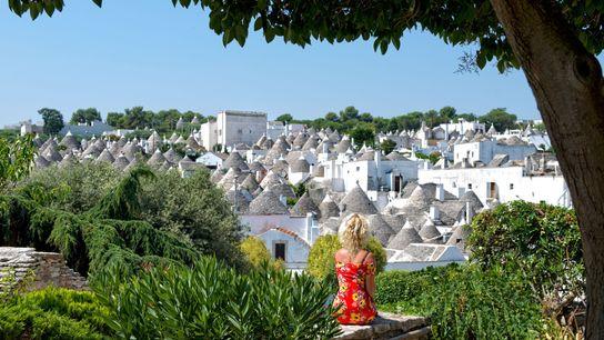 Une touriste admire la vue sur les trulli d'Alberobello, une petite ville des Pouilles en Italie. ...