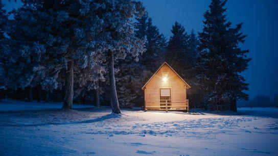 Alors que la nuit approche, une chaude lueur illumine l'une des huttes de montagne rustiques de ...