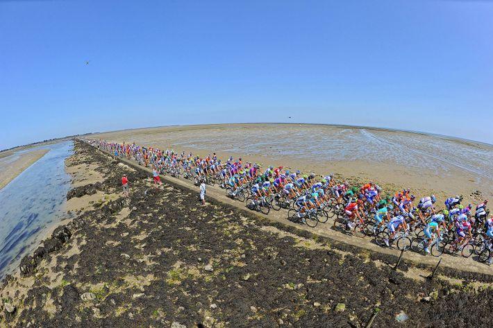 Les cyclistes du Tour de France traversent le passage du Gois, un chemin sur la côte ...