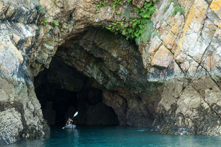Un kayakiste dans une grotte marine de la presqu'île de Crozon.