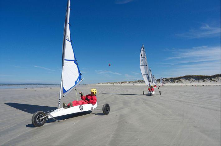Des « chars-à-voilistes » se promènent sur une plage de Bretagne à bord des véhicules à ...