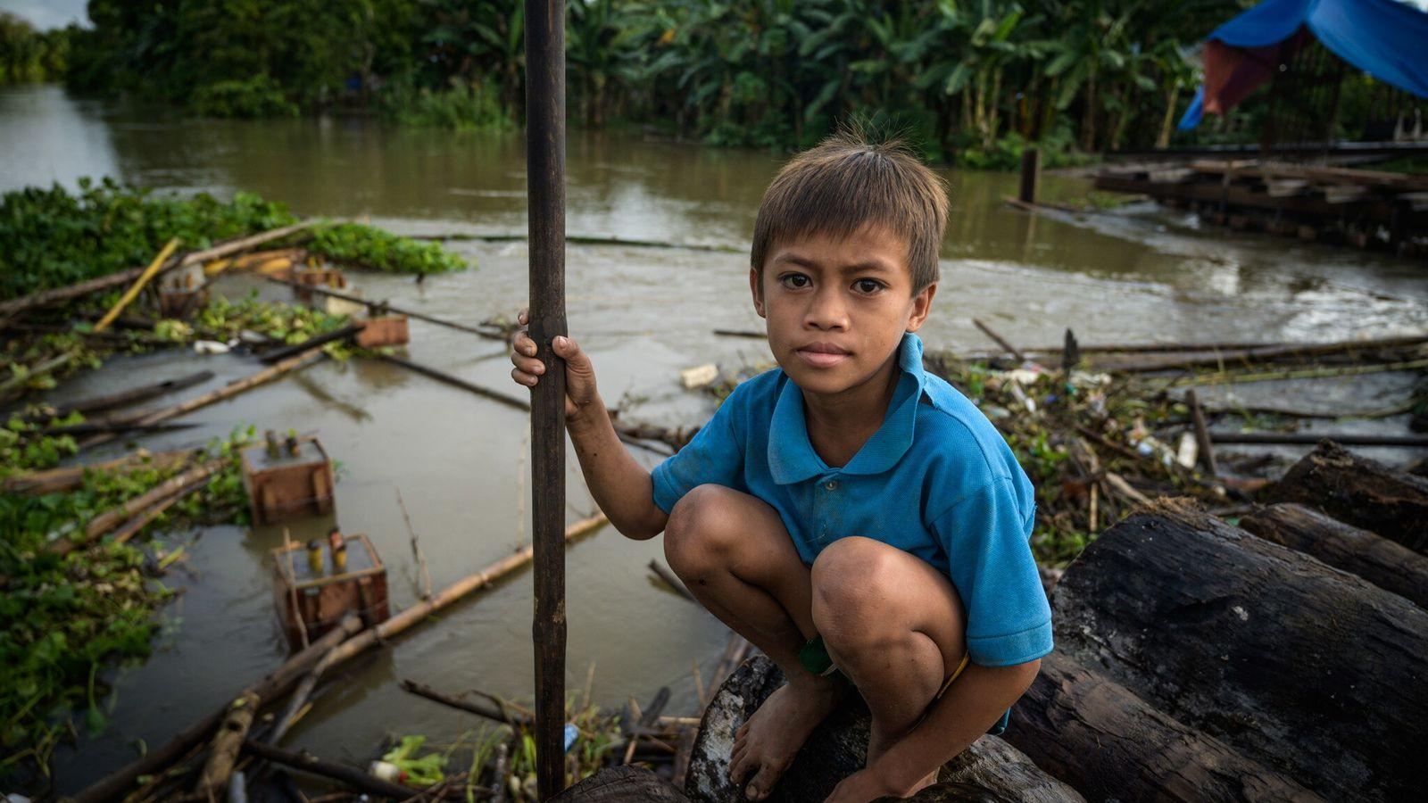 Un enfant Manobo est assis sur les restes d'une construction routière érigée pour acheminer l'huile de ...