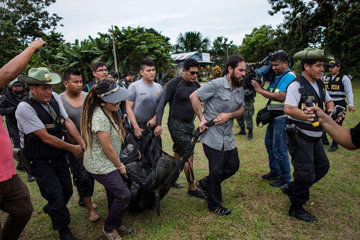 Des policiers et des vétérinaires portent un lamantin jusqu'à un bateau qui l'attend. L'animal était détenu ...