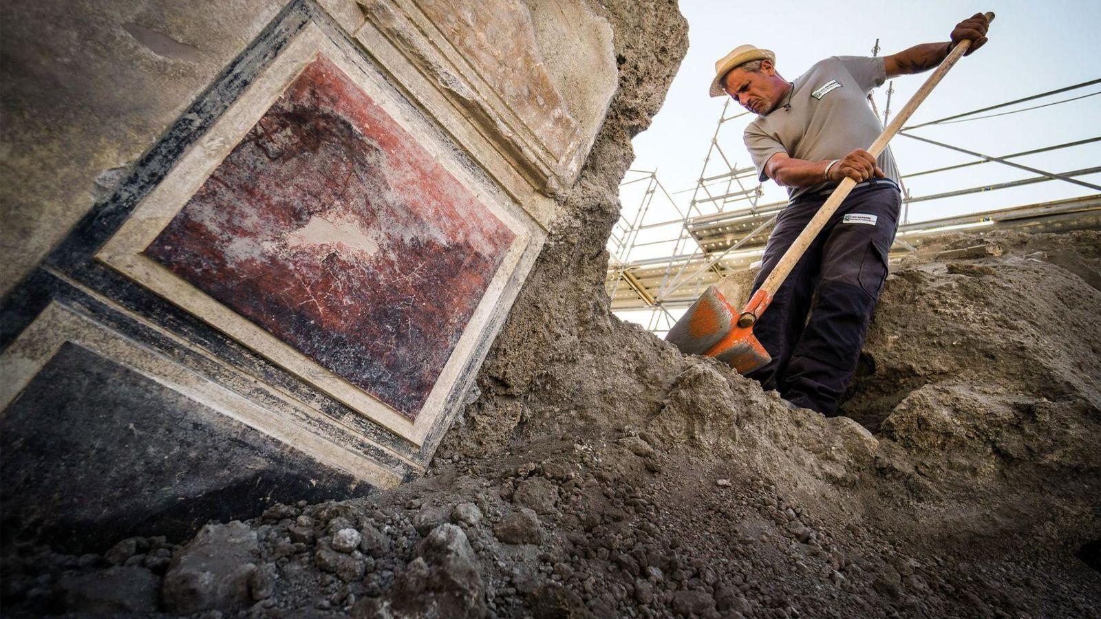 Un travailleur retire les fragments de lave (lapilli) de l'atrium de la maison d'Orion dans la ...
