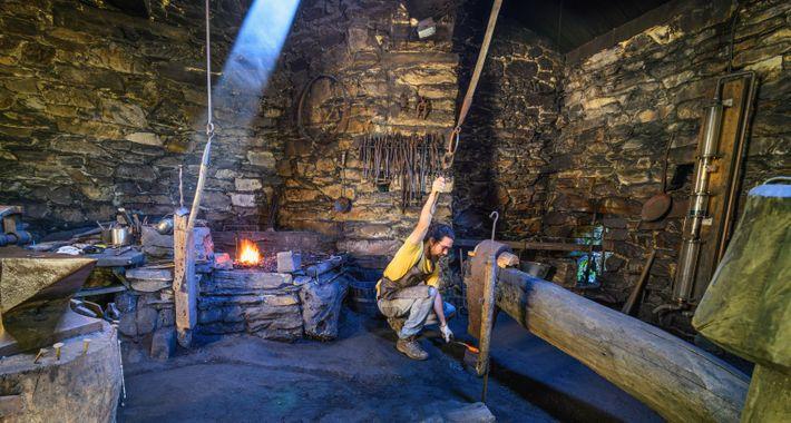 Un forgeron, ou ferreiro, présente les outils et méthodes traditionnels encore utilisés pour fabriquer le fer ...