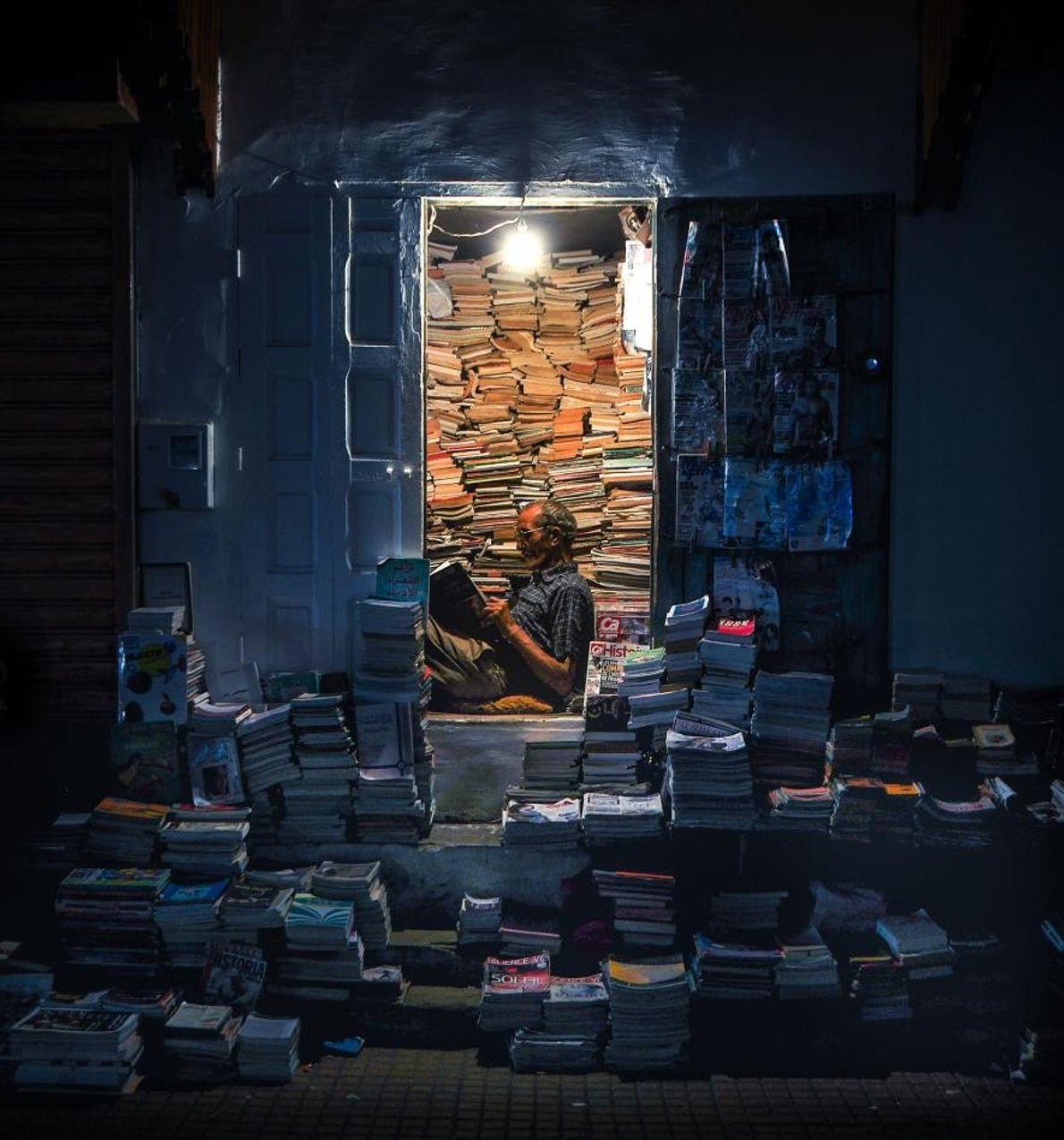 À Rabat, la capitale du Maroc, un kiosquier bouquine au milieu des piles de magazines.