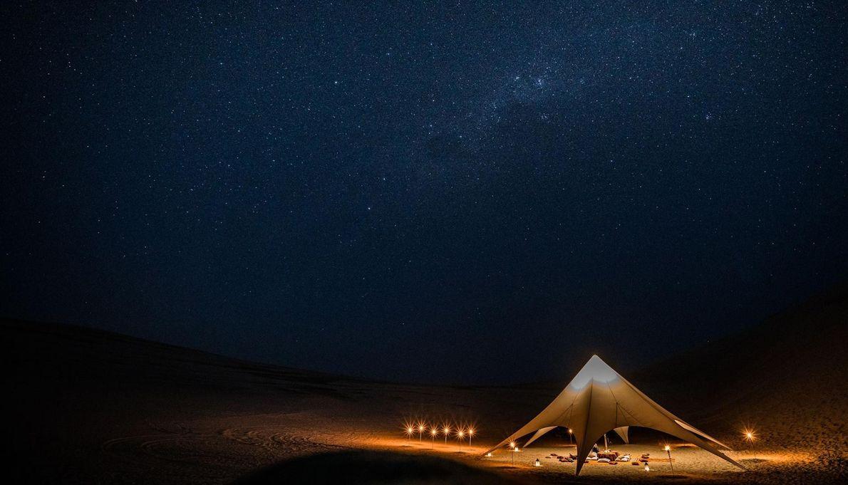 Au Pérou, dans le désert non loin de Paracas, une tente-repas illuminée se détache dans la ...