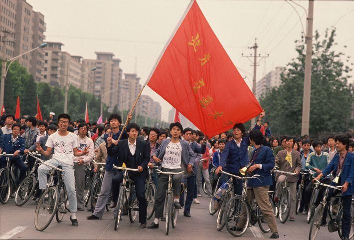 À Pékin, un groupe d'étudiants chinois à vélo parcourt la ville en agitant des banières pour ...