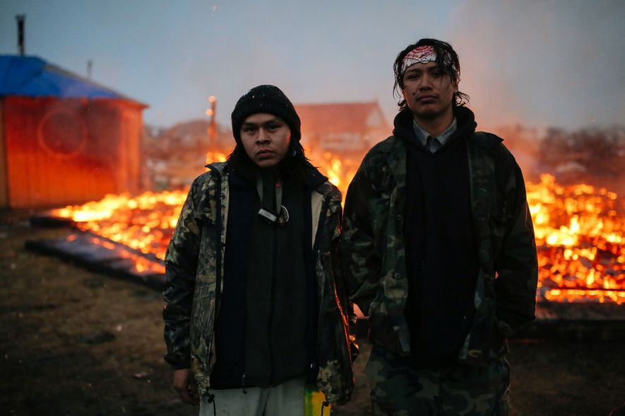 À Cannon Ball, dans le Dakota du Nord, deux jeunes militants pour les droits à l'eau sont photographiés devant une case en terre en feu, une habitation Navajo traditionnelle. Pendant des mois, les manifestants ont occupé la réserve Standing Rock pour protester contre le Dakota Access Pipeline. Contraint de partir en février 2017, des occupants ont mis le feu à certaines parties du site.